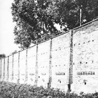 Бывшая стена концлагеря Равенсбрюк, служащая границей мемориального ансамбля. У подножия - братская могила